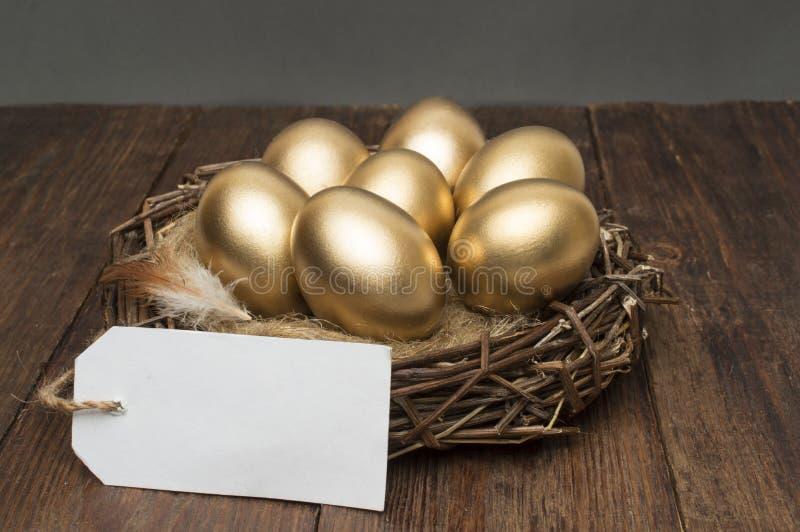 Nisten Sie mit goldenen Eiern mit einem Tag und setzen Sie f?r Text auf einen h?lzernen Hintergrund Das Konzept des erfolgreichen stockbild