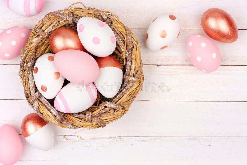 Nisten Sie mit rosafarbenen Gold-, rosa und weißen Ostereiern gegen weißes Holz stockfotografie