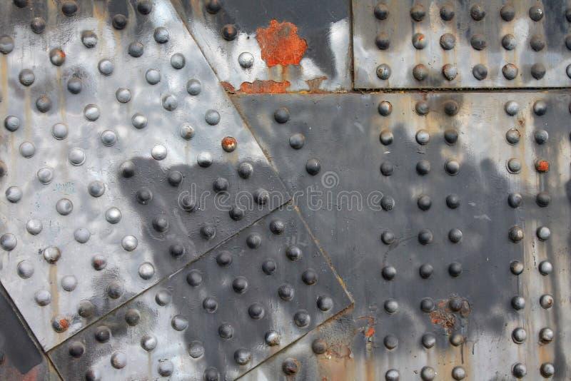 Nitar och bakgrund för rosthorisontalindustriell stålbalk royaltyfri bild