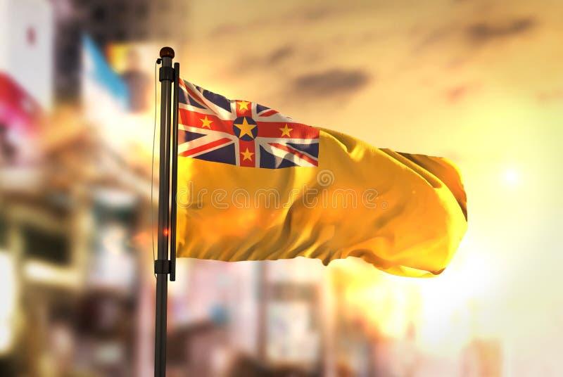 Niue Flag Against City Blurred Background At Sunrise Backlight. Sky royalty free stock image