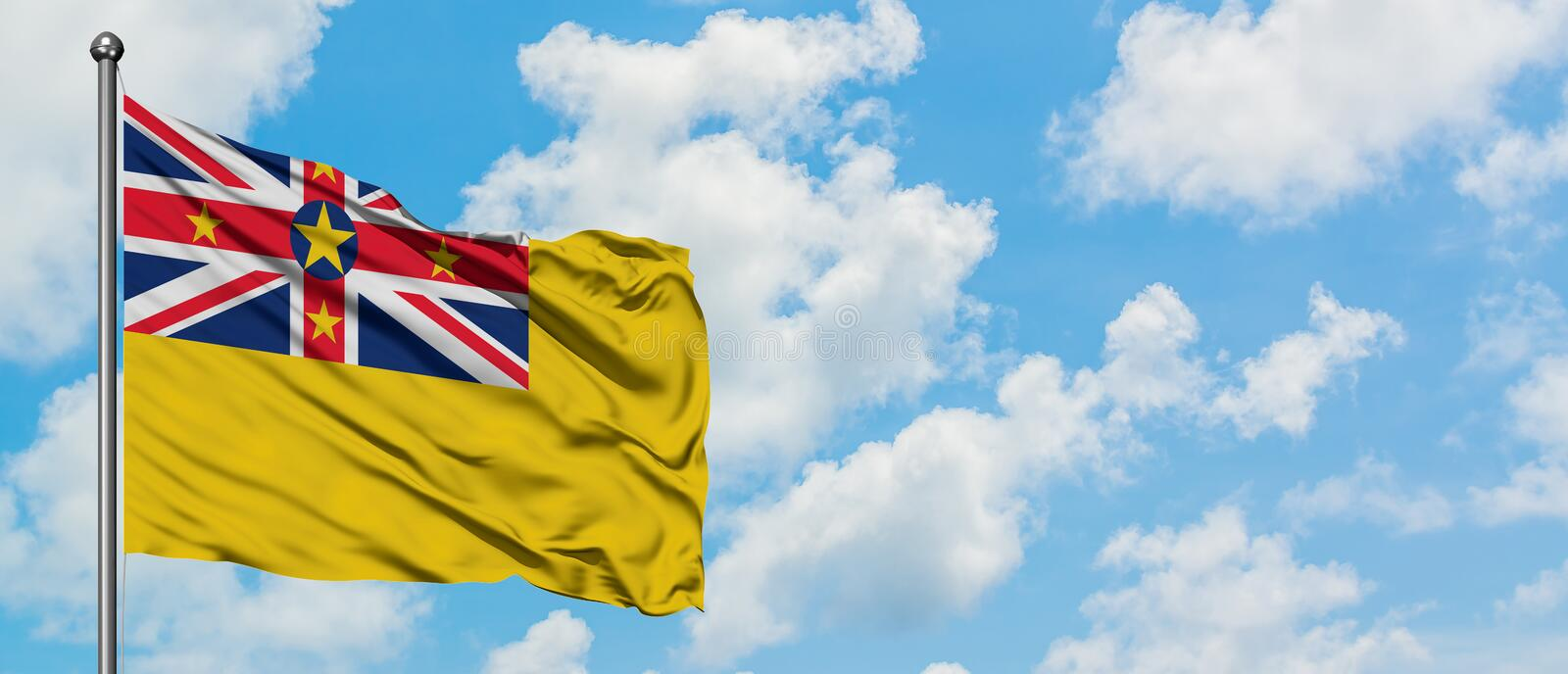 Niue flag waving in the wind against white cloudy blue sky. Diplomacy concept, international relations.  royalty free stock photography