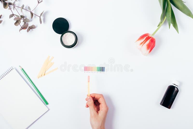 Nivå för pH för kvinnakontrollskönhetsmedel, genom att använda lackmuspapper arkivfoton