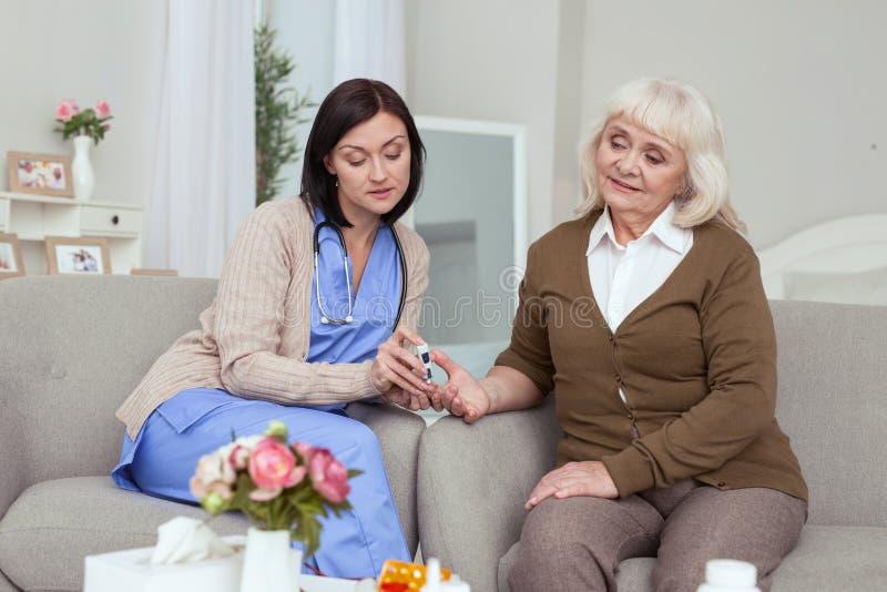Niveau de contrôle de glucose de belle infirmière attentive images stock