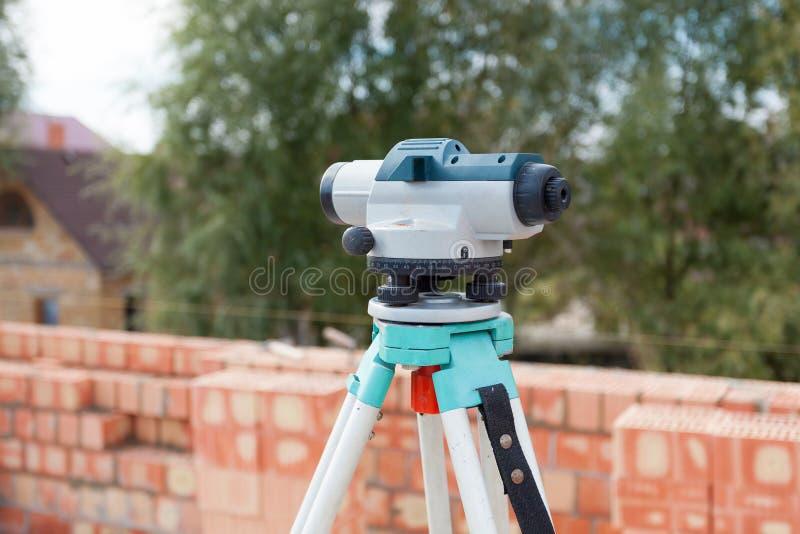 Niveau ou théodolite optique d'équipement d'arpenteur dehors au chantier de construction photographie stock libre de droits