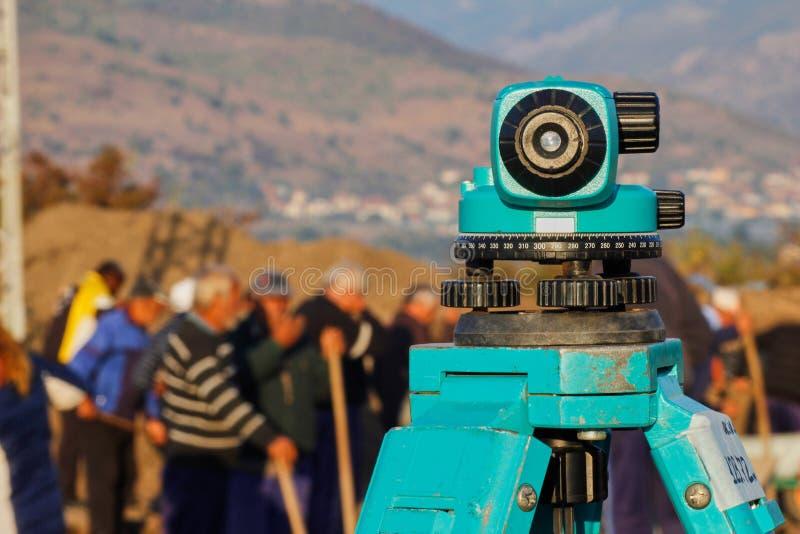 Nivel óptico con los trabajadores en el fondo fotografía de archivo libre de regalías