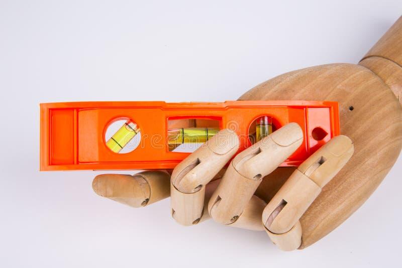 Nivel de la herramienta de madera de la mano y del edificio fotografía de archivo