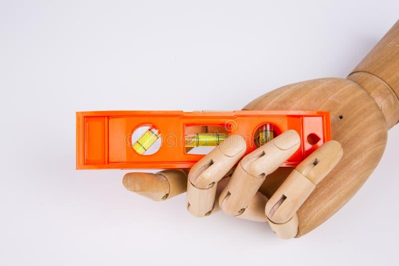 Nivel de la herramienta de madera de la mano y del edificio foto de archivo