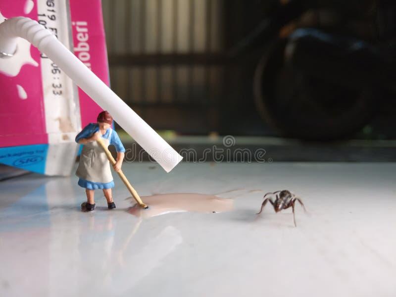 Nivel del ojo, mini figura mujer del juguete que limpia el chocolate caliente derramado del UHT en el piso, bebida por una hormig foto de archivo libre de regalías