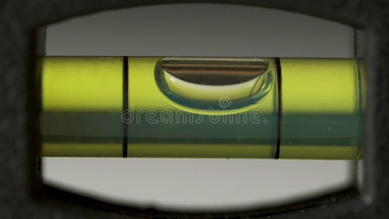 Nivelación del primer de la burbuja del ` s del instrumento Macro del nivel de alcohol del ` s del carpintero Edificios y nivel d foto de archivo