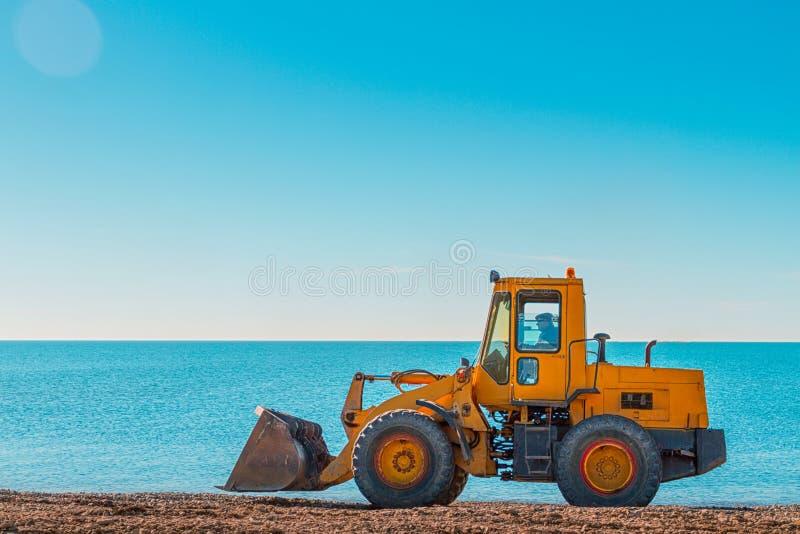 Niveladora amarilla en el fondo del cielo azul y del mar claros Copie el espacio imagenes de archivo