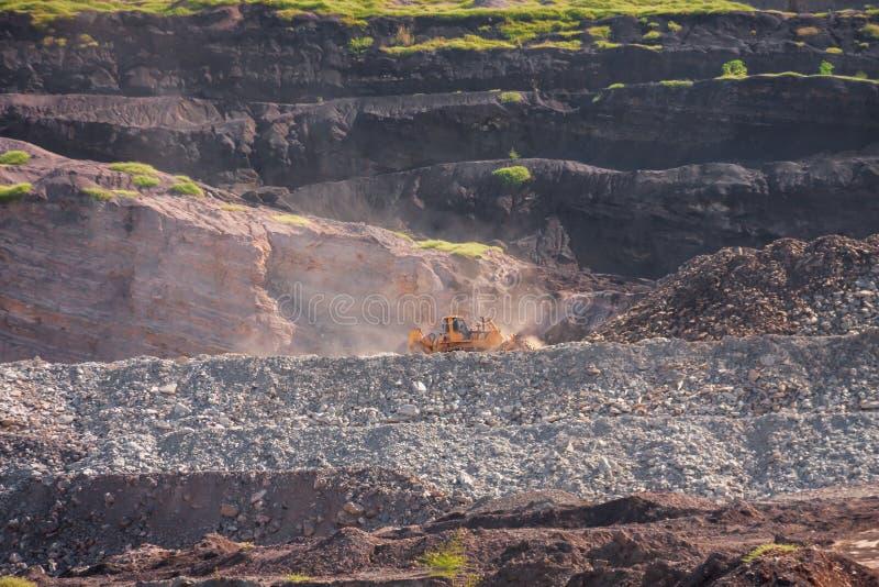 Niveladora amarilla en la explotación minera foto de archivo
