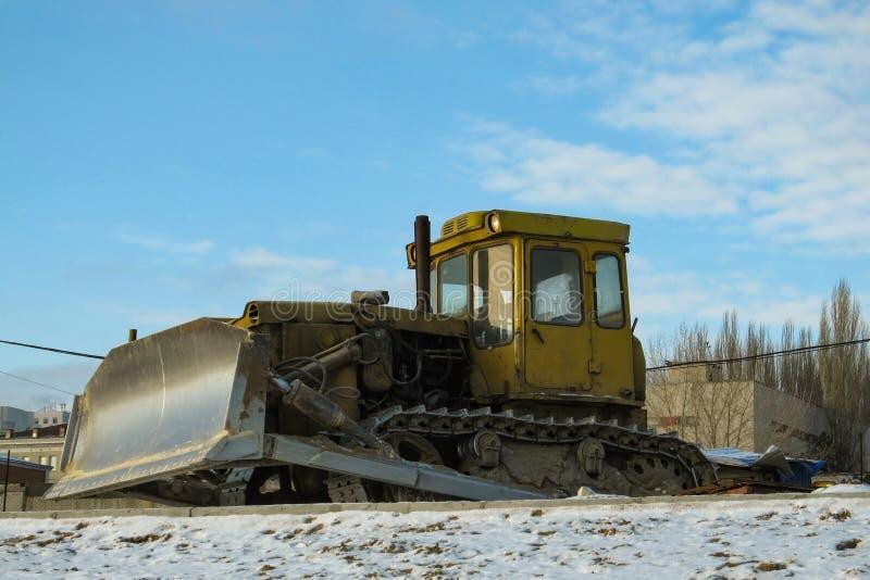 Niveladora amarilla sucia en el camino del invierno porque construcción parada foto de archivo