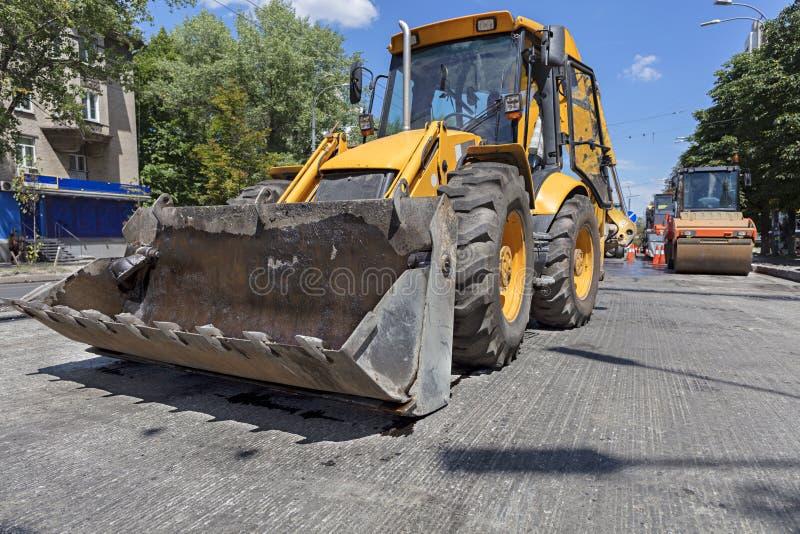 Niveladora de la construcción pesada y rodillo vibrante durante la construcción de carreteras imagenes de archivo