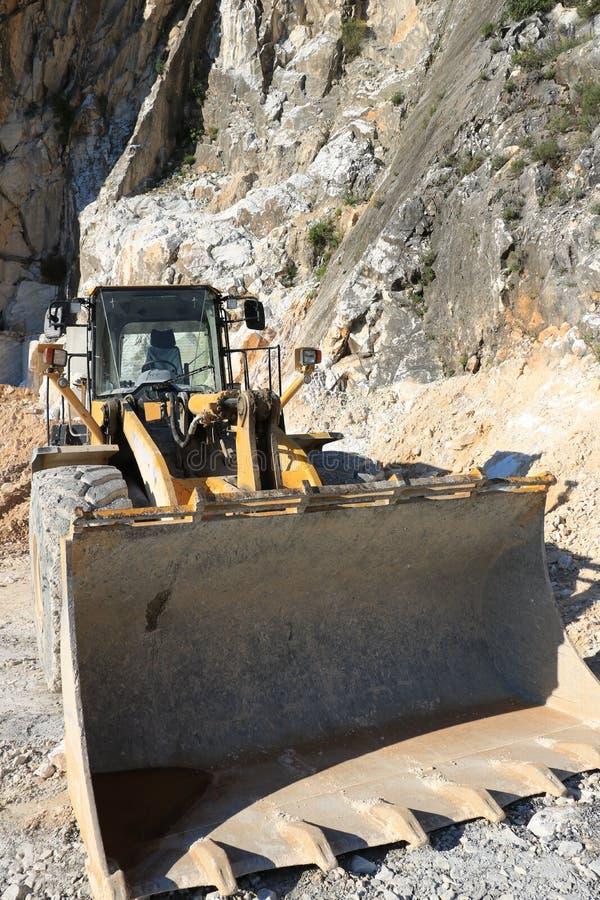 Niveladora en una mina del m?rmol de Carrara Una pala mec?nica grande fotos de archivo