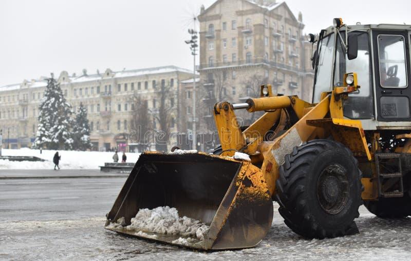 Niveladora para la retirada de la nieve en una calle del invierno foto de archivo