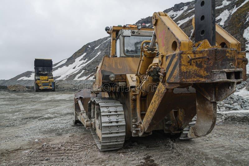 Niveladora potente de la mina y camión volquete del gigat que actúa en la mina de la apatita en la región de Murmansk foto de archivo