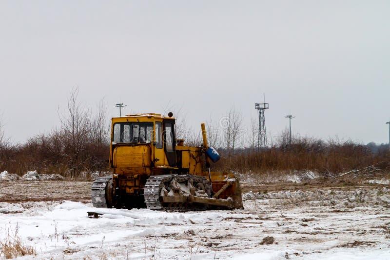Niveladora vieja en un campo inculto en invierno fotos de archivo