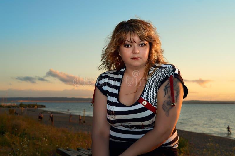 Nivelamento sobre o Volga - a jovem mulher bonita senta-se no banco do Rio Volga & do x28; Russia& x29; fotos de stock royalty free
