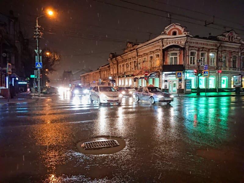 Nivelando a arquitetura da cidade no tempo chuvoso Carros e luzes da noite Cidade de Saratov, Rússia fotos de stock royalty free