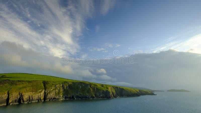 Nivelando a luz nos penhascos de Ceredigion e a ilha do casaco de lã de Mwnt, Gales imagens de stock