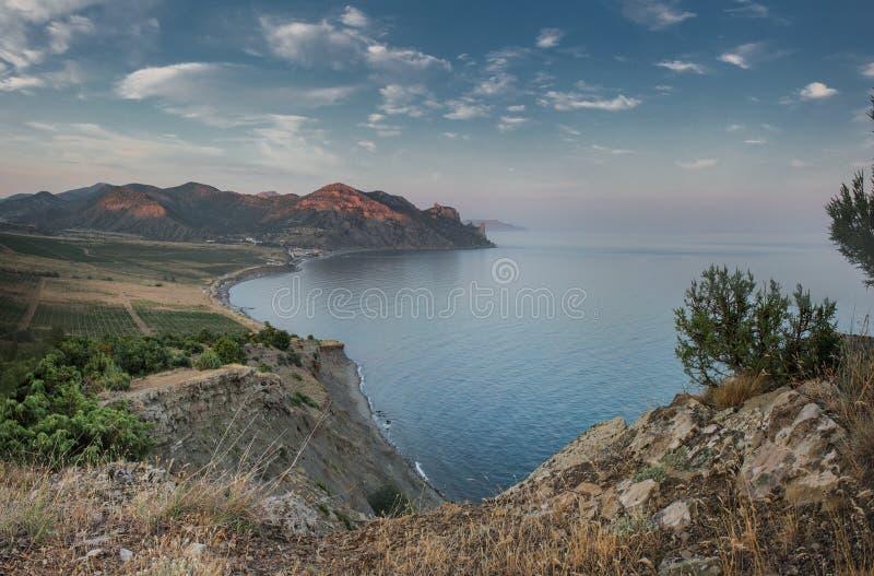 Nivelando o crepúsculo em uma baía quieta no pé das montanhas fotografia de stock