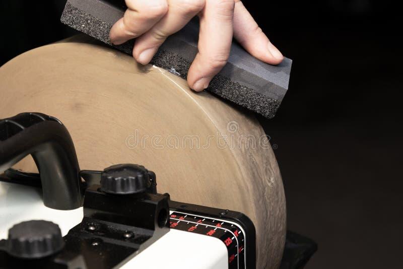 Nivelando a pedra de moedura com uma lâmina para apontar facas fotos de stock royalty free
