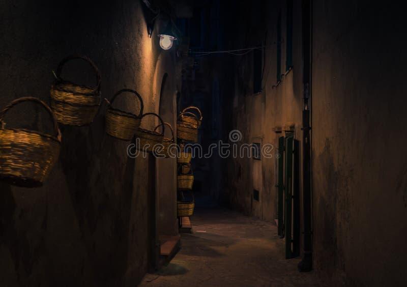 Nivelando a rua com as cestas brilhantes das lanternas na parede, Tropea, AIE imagem de stock