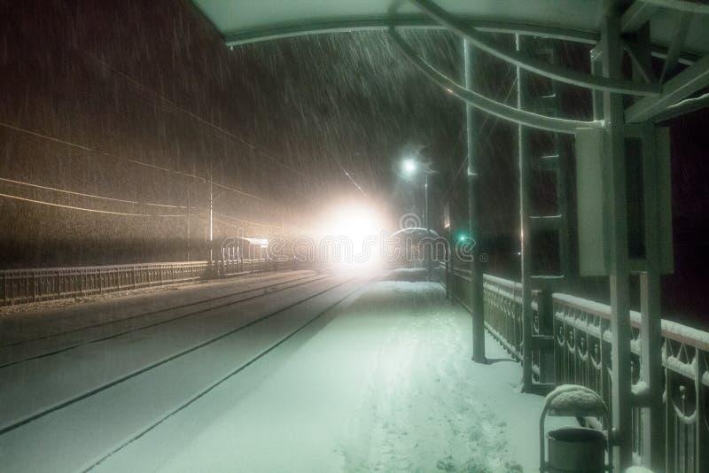 Nivelar o trem chega na estação snowfall imagem de stock