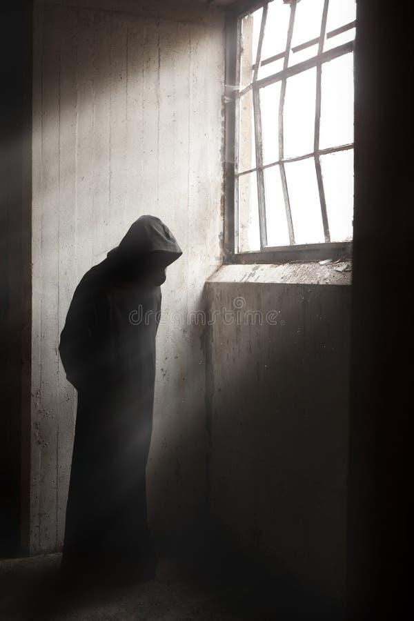 Żniwiarki czekanie w ciemnym zaniechanym budynku obraz stock