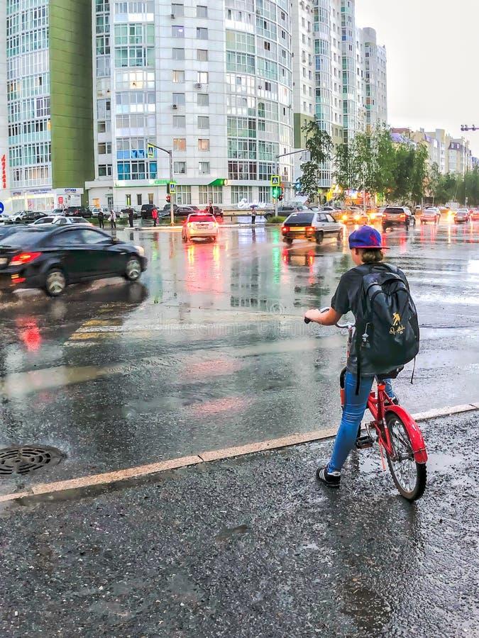 Nizhnevartovsk, czerwiec 5, 2019: chłopiec czekać na zielonego światła ruchu na rowerze obraz stock
