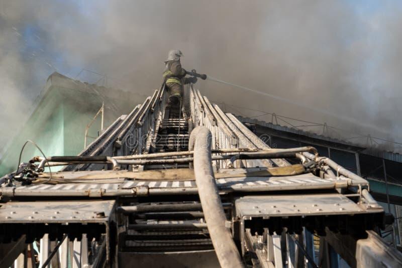 Nizhnevartovsk, Russie - 1er juillet 2019 : Le toit d'une maison résidentielle brûle les sapeurs-pompiers s'éteignent un feu sur photographie stock