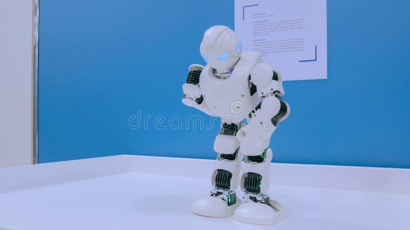 White humanoid robot dancing. NIZHNIY NOVGOROD, RUSSIA - August 7, 2017: The Exhibition Park Of Robots. White humanoid robot dancing at technology show. Future stock photo