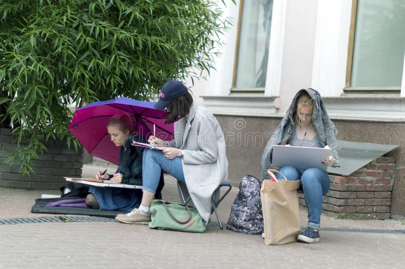 Young artists make sketches of the facade of the building. stock images