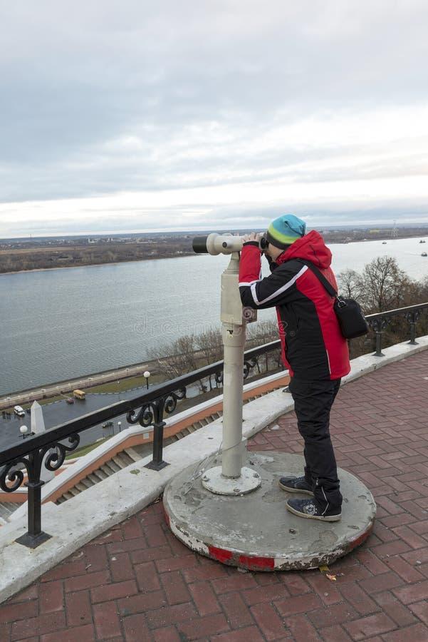Nizhny Novgorod Ryssland - November 11, 2015 Pojken ser till och med kikare på Volga River från utkiken royaltyfria foton