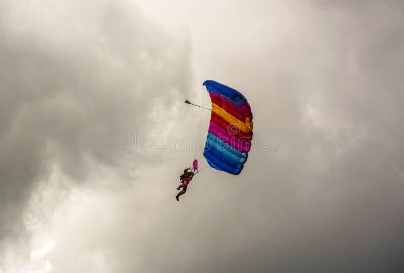 NIZHYN, УКРАИНА - 17-ОЕ СЕНТЯБРЯ 2016: Одиночный skydiver на красочном парашюте под пасмурным ненастным небом стоковые фото