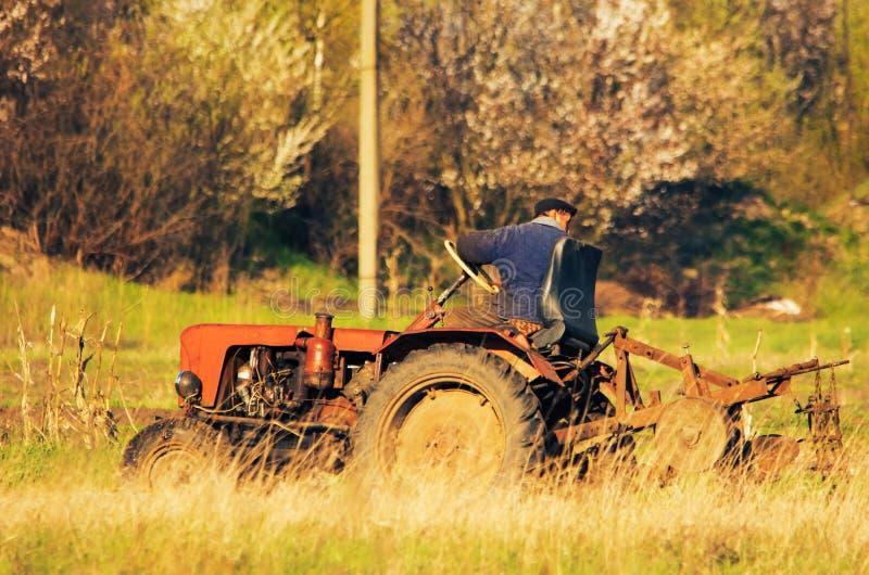 NIZHYN, DE OEKRAÏNE - APRIL 21, 2017: De tractor die de aarde in de herfst ploegen om de wintertarwe te zaaien Zachte nadruk royalty-vrije stock afbeelding