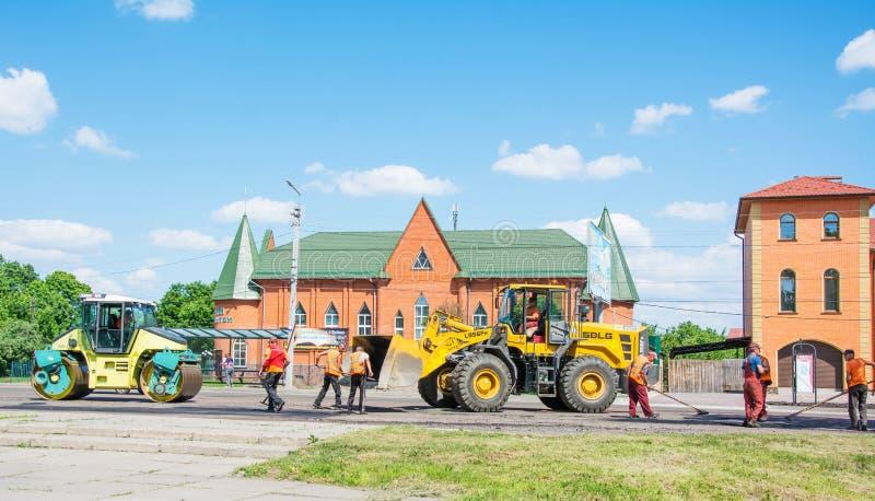 NIZHYN, UKRAINE - 25 MAI 2018 : Brigade de travail réparant la route utilisant la machine à paver d'asphalte de chenille complète photos stock