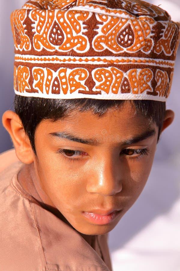 NIZWA, OMAN - FEBRUARI 3, 2012: Het portret van een weinig Omani jongen kleedde traditioneel het bijwonen van de Geitmarkt stock foto