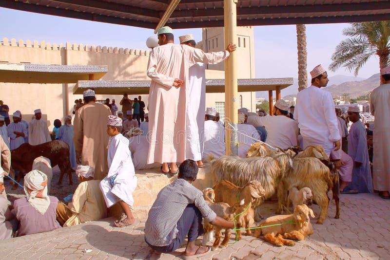 NIZWA, OMAN - FEBRUARY 3, 2012: Omani men traditionally dressed attending the Goat Market in Nizwa royalty free stock photo