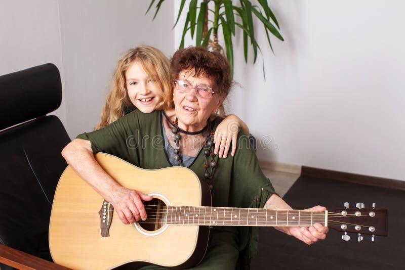 90 ??njarigengrootmoeder om de gitaar te spelen stock afbeelding