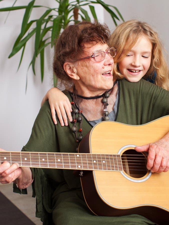 90 ??njarigengrootmoeder om de gitaar te spelen stock foto