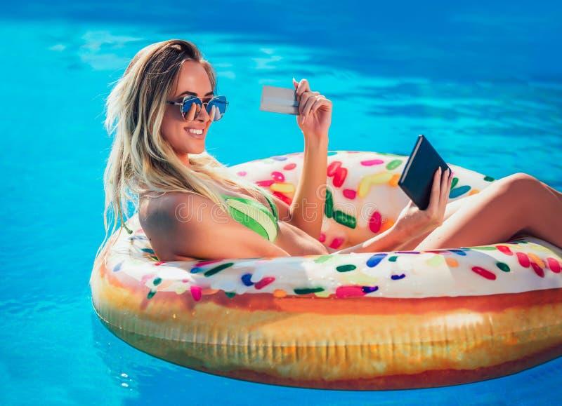 Njoying solbrännakvinna i bikini på den uppblåsbara madrassen i simbassängen som använder den digitala minnestavlan och kreditkor fotografering för bildbyråer