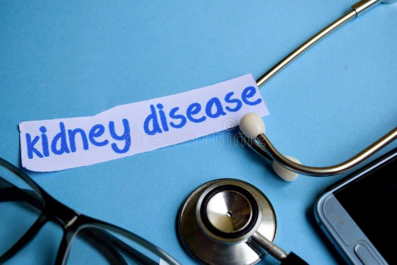 Njursjukdominskrift med sikten av stetoskopet, glasögon och smartphonen på den blåa bakgrunden royaltyfri fotografi