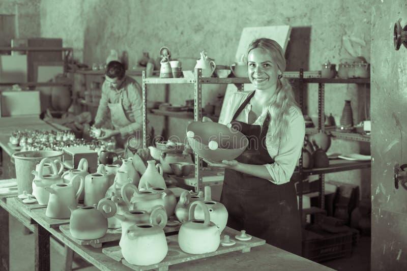Njutbar kvinnlig hantverkare som har keramik i seminarium royaltyfri foto
