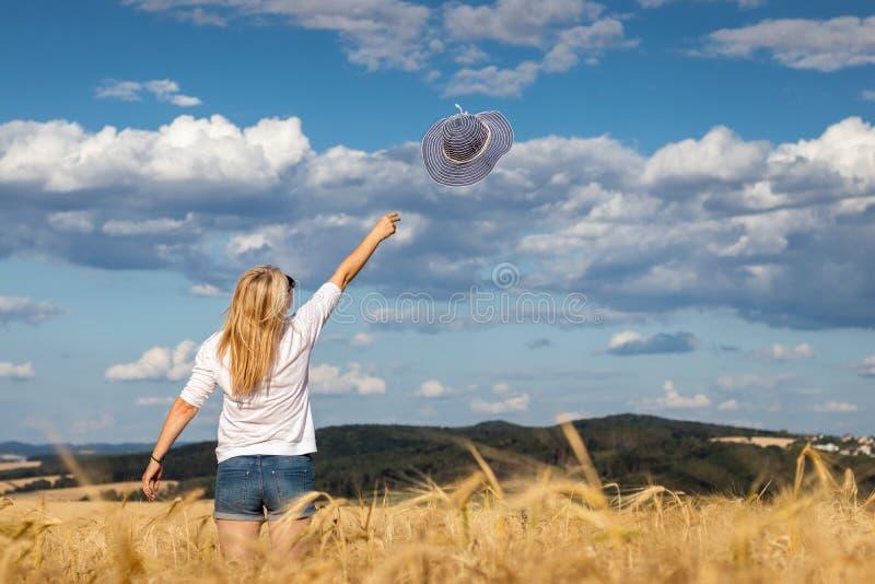 Njutning av sommar Bekymmerslöst kvinnaanseende i vetefält fotografering för bildbyråer