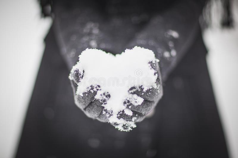 Heart from the snow in the arms. royalty free stock photos
