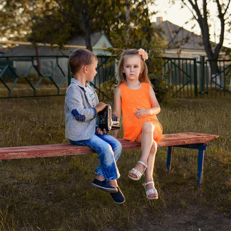 Photo session of a little photographer. NnPhoto session of a little boy and girl with an old photo camera at sunset royalty free stock image