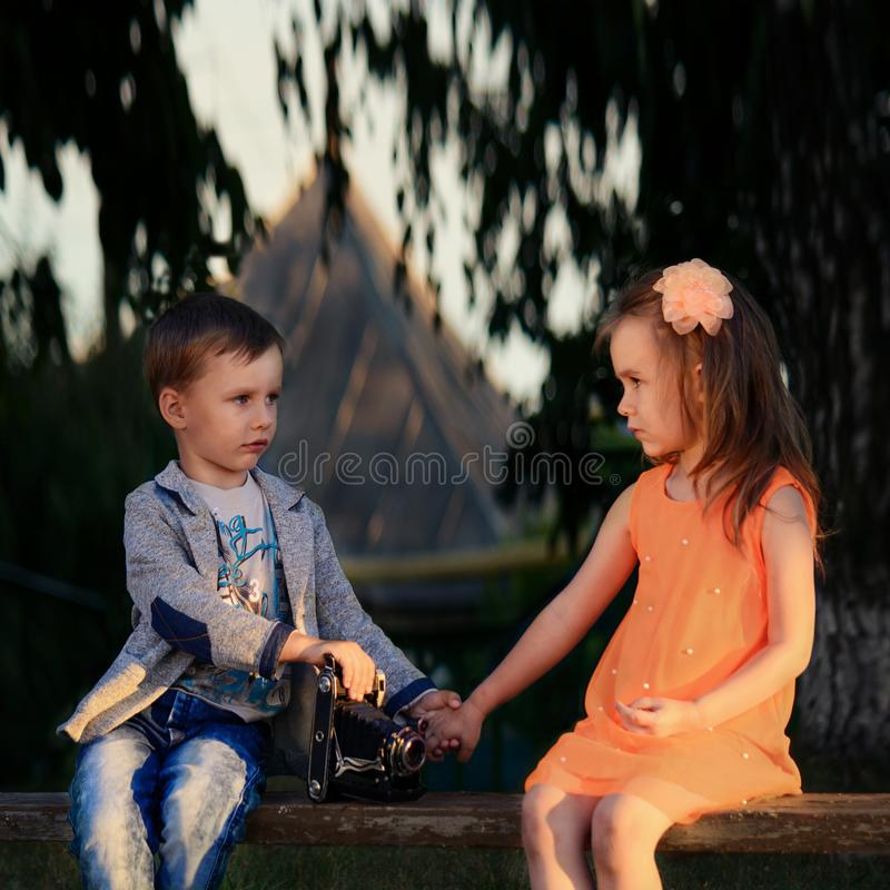 Photo session of a little photographer. NnPhoto session of a little boy and girl with an old photo camera at sunset royalty free stock photo