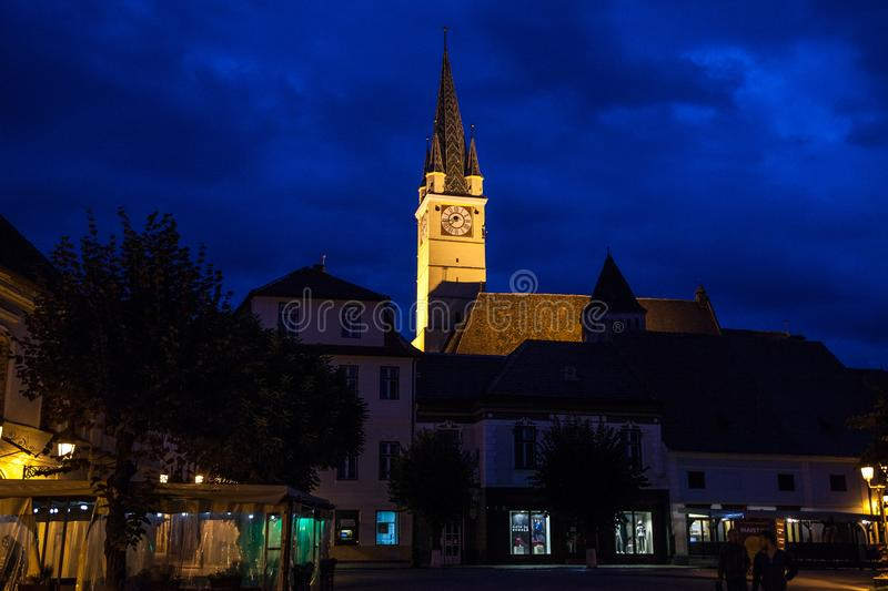 Saint Margaret Sf. Margareta church in the evening seen from the main square of Medias, one of the main cities of Transylvania royalty free stock photography