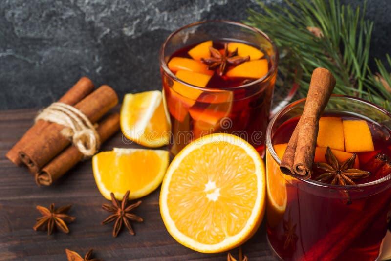 Noël a chauffé le vin rouge avec des épices et des fruits sur une table rustique en bois Boisson chaude traditionnelle au temps d photographie stock